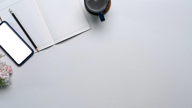 Widok z góry na minimalny obszar roboczy z pustym notatnikiem, smartfonem i filiżanką kawy