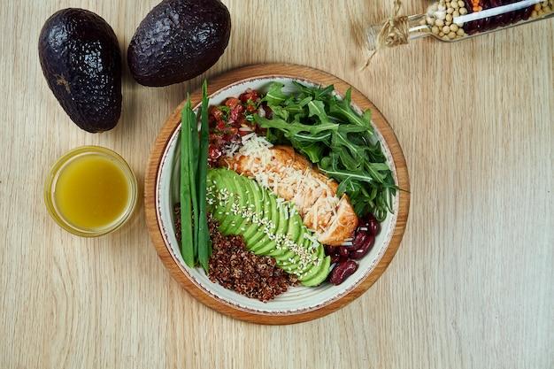 Widok z góry na miskę buddy z kurczakiem, awokado, suszonymi pomidorami, komosą ryżową, rukolą, fasolą. smaczne i zdrowe jedzenie na obiad. płaskie jedzenie