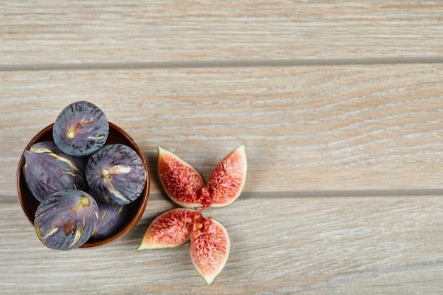 Widok z góry na miskę czarnych fig i plastry fig na drewnianym stole