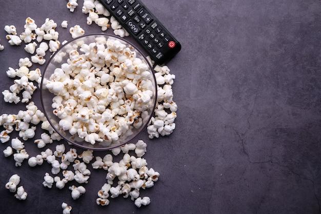 Widok z góry na miskę popcornu i pilota do telewizora na czarnym tle