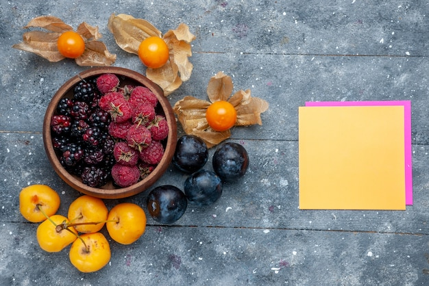 Widok z góry na miskę z jagodami świeże dojrzałe owoce z żółtymi wiśniami i śliwkami na szarym, jagodowym świeżym łagodnym lesie