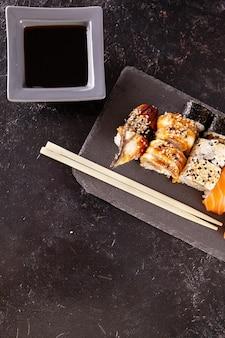 Widok z góry na mix różnych rolek sushi na czarnym tle w studio