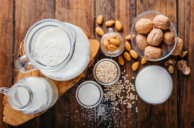 Widok z góry na mleko roślinne na tle drewna, mleko migdałowe, mleko orzechowe, mleko ryżowe i mleko kokosowe