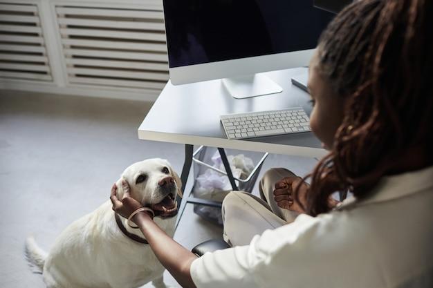 Widok z góry na młodą afroamerykankę pieszczącą psa podczas pracy w biurze przyjaznym dla zwierząt...