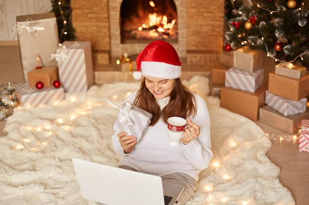 Widok z góry na młodą, dorosłą kobietę siedzącą na podłodze ze swoim laptopem, z radosnym wyrazem twarzy, pijącą herbatę z kubka podczas rozmowy wideo, pokazującą obecne pudełko do kamery internetowej.