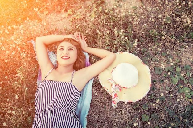 Widok z góry na młodą kobietę leżącą blisko jej kapelusz