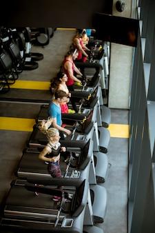 Widok z góry na młodych ludzi biegających na bieżniach w nowoczesnej siłowni