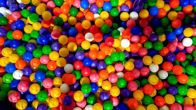 Widok z góry na mnóstwo kolorowych plastikowych piłek w basenie na placu zabaw w parku rozrywki