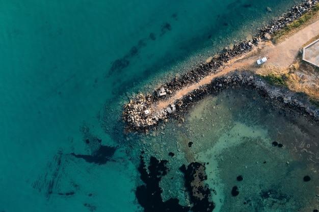 Widok z góry na molo zbudowane z dużych kamieni wpadających do morza z czystą turkusową wodą