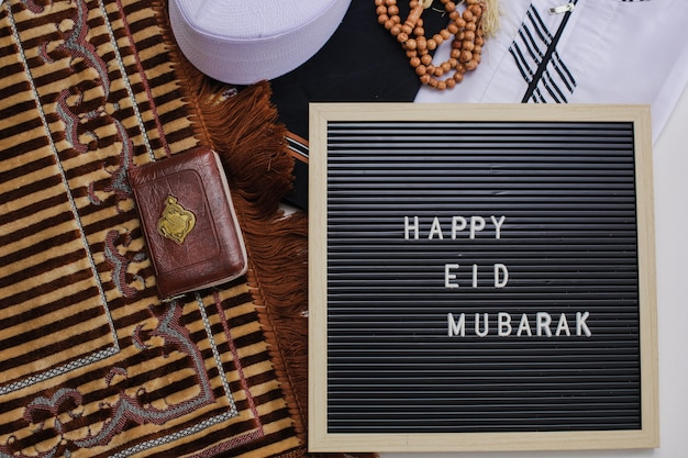 Widok z góry na muzułmańską sukienkę i koraliki modlitewne ze świętą księgą al koranu i tablicą z napisem happy eid mubarak istnieje arabska litera, która oznacza świętą księgę