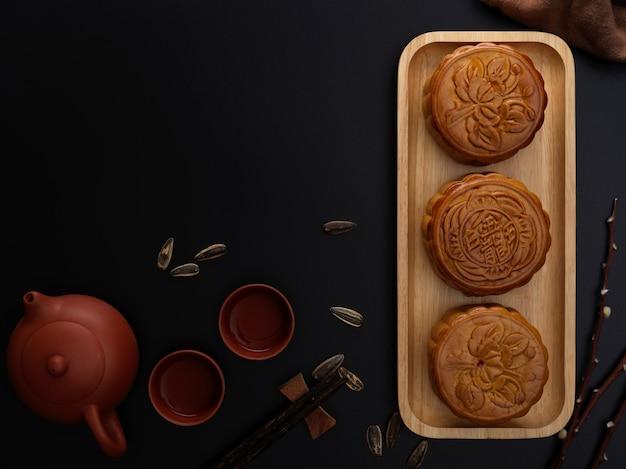 """Widok z góry na nakrycie stołu z tradycyjnymi ciastami księżycowymi, zestawem do herbaty i miejscem na kopię podczas festiwalu księżyca. chińskie znaki na księżycowym cieście oznaczają w języku angielskim """"pięć ziaren i pieczeń wieprzową"""""""