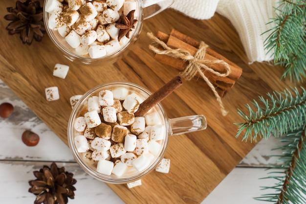 Widok z góry na napój czekoladowy z piankami, laski cynamonu, szyszki i gałęzie świerkowe. koncepcja przytulnych świąt bożego narodzenia i nowego roku.