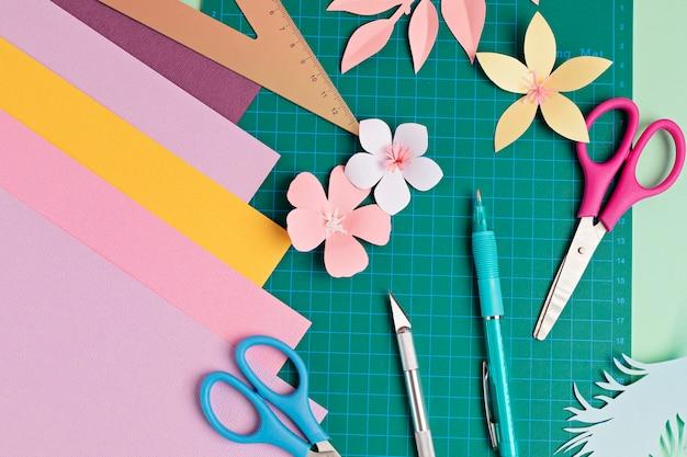 Widok z góry na narzędzia do cięcia papieru, nożyczki, nożyk, matę do cięcia i przedmioty wykonane z papieru