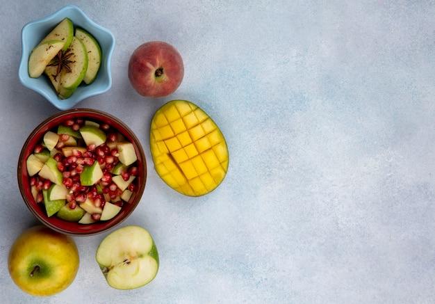 Widok z góry na nasiona granatu i posiekane jabłka w czerwonej misce z pokrojonym mango i świeżymi owocami na białej powierzchni