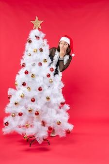 Widok z góry na nastrój noworoczny z zaskoczoną piękną dziewczyną w czarnej sukience z czapką mikołaja chowającą się za choinką