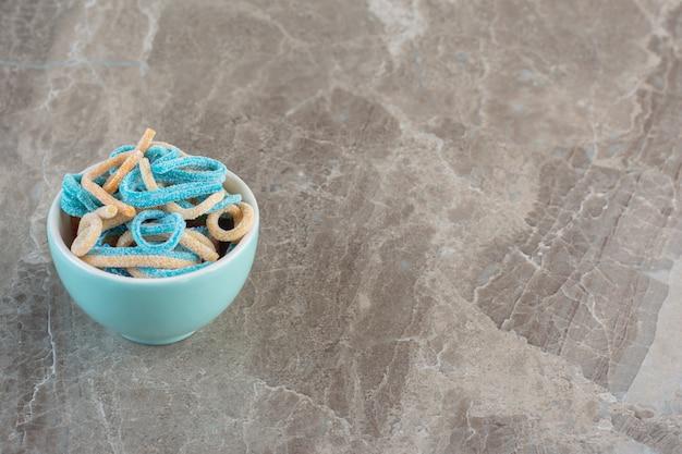 Widok z góry na niebieską miskę pełną kolorowych cukierków wstążki.