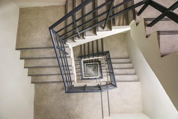 Widok z góry na nieskończone schody spiralne, droga do sukcesu, sposób na ucieczkę, schody ewakuacyjne.
