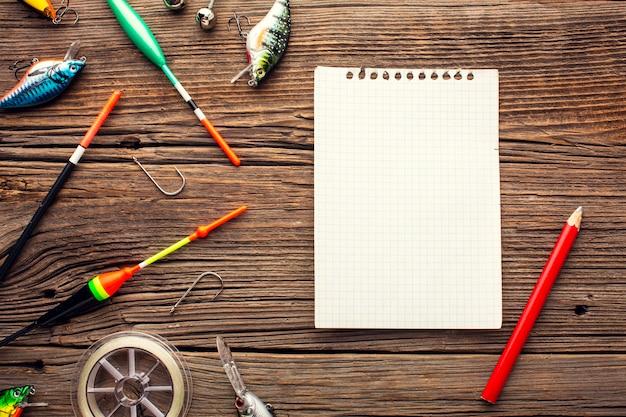 Widok z góry na niezbędne artykuły wędkarskie z notatnikiem i ołówkiem