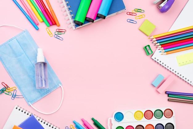 Widok z góry na niezbędne przybory szkolne z ołówkami i maską medyczną