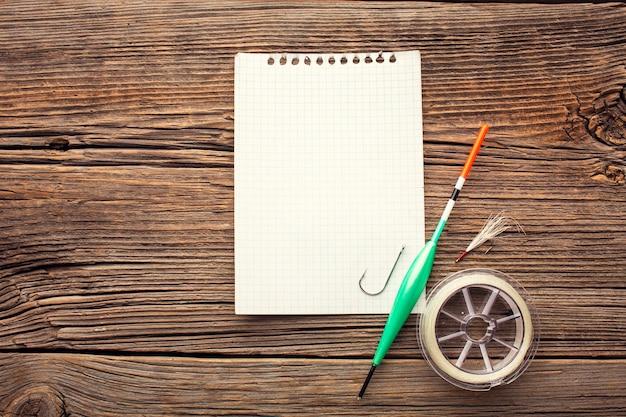 Widok z góry na niezbędny sprzęt wędkarski z notatnikiem i hakiem