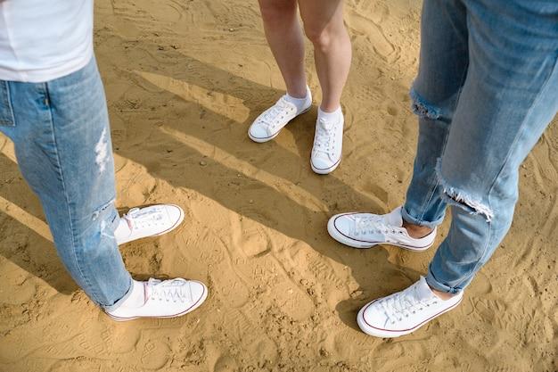 Widok z góry na nogi młodych ludzi w białych trampkach na piasku. buty selfie z góry.