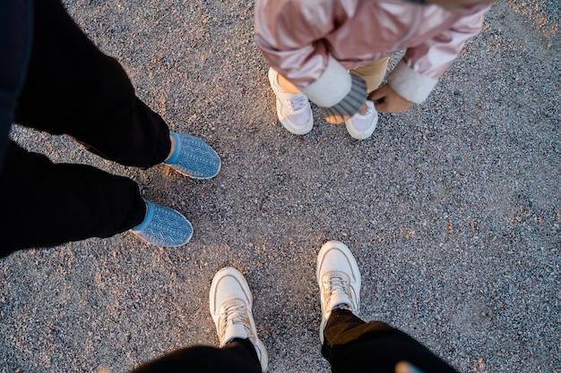 Widok z góry na nogi rodziny na ziemi na zewnątrz. spajanie czasu razem. proste rzeczy. wysokiej jakości zdjęcie