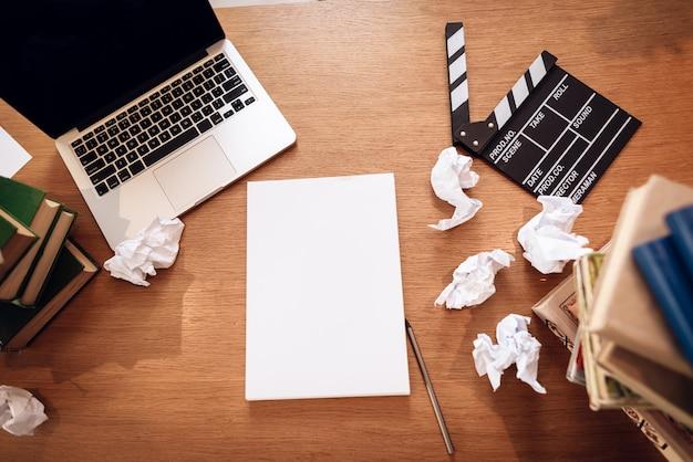 Widok z góry na notatki papieru przez laptopa otoczony książkami.