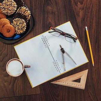Widok z góry na notatnik, artykuły papiernicze, narzędzia do rysowania i kilka filiżanek kawy.