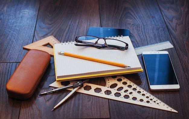 Widok z góry na notatnik, artykuły papiernicze, narzędzia do rysowania i kilka szklanek. improwizować.