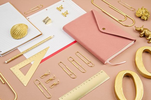 Widok z góry na notatnik i złote materiały biurowe.