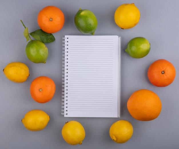 Widok z góry na notatnik przestrzeni kopii z pomarańczy, cytryny i limonki na szarym tle