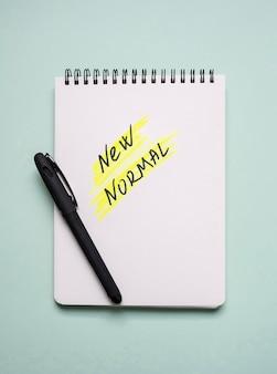 Widok z góry na notatnik z nowym normalnym i piórem