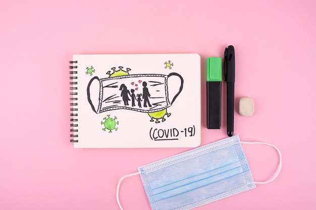 Widok z góry na notebook z maską medyczną i długopisem