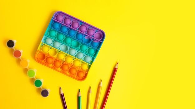 Widok z góry na nową sensoryczną zabawkę - tęcza pop z dziecięcymi rzeczami po bokach - wielokolorowe ołówki i farby. antystresowa zabawka dla dziecka i dorosłych, duży baner z miejscem na kopię.