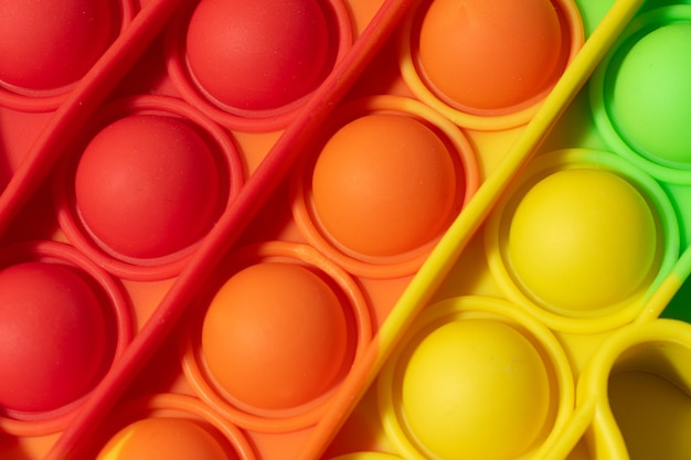 Widok z góry na nową zabawkę sensoryczną - pop it.kolor tęczowy, makrofotografia bąbelków. forma silikonowa