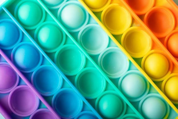 Widok z góry na nową zabawkę sensoryczną - pop it.kolor tęczowy, wklęsłe i wypukłe bąbelki.silikonowa forma.