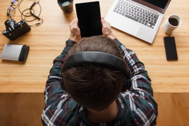 Widok z góry na nowoczesne miejsce pracy profesjonalnego artysty lub fotografa, pracującego na komputerze przenośnym, tablecie, twórcy muzyki, wnętrzach domowych. proces twórczy