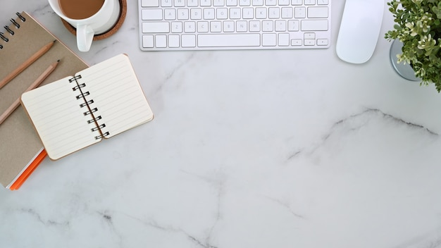 Widok z góry na nowoczesne miejsce pracy z notebookiem, klawiaturą, filiżanką kawy i rośliną domową na marmurowym tle.