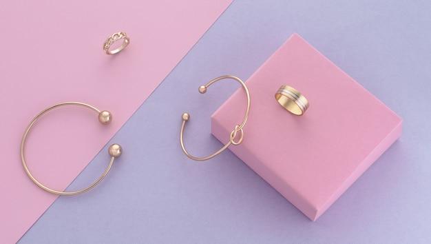 Widok z góry na nowoczesne złote akcesoria na różowym i fioletowym tle pastelowych kolorów