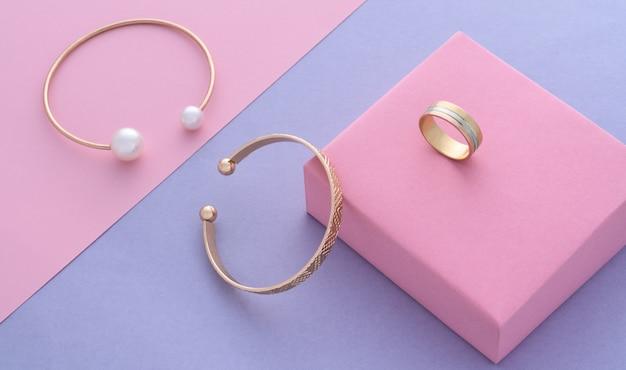 Widok z góry na nowoczesne złote bransoletki i pierścionek na tle papieru w pastelowych kolorach z miejscem na kopię