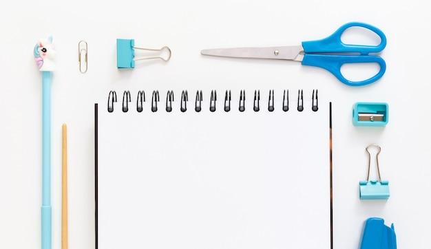 Widok z góry na nowoczesny biały niebieski pulpit biurowy z przyborami szkolnymi i papeterią na stole wokół pustej przestrzeni dla tekstu. powrót do koncepcji szkoły płaskiej z makietą