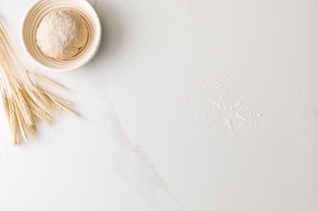 Widok z góry na odpoczywające ciasto chlebowe w misce chleba w marmurowym stole z pszenicy i mąki z miejscem na tekst
