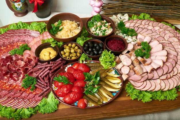 Widok z góry na ogromny drewniany talerz pełen przystawek mięsnych w plasterkach szynka salami