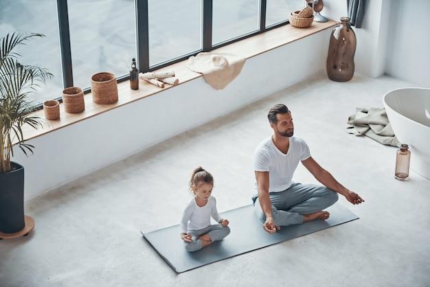 Widok z góry na ojca i córkę uprawiających jogę siedząc w pozycji lotosu w domu