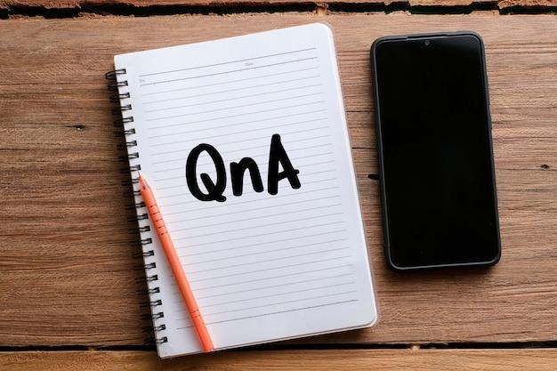 Widok z góry na okulary i deskę napisany tekstem q i a na drewnianym tle. koncepcja biznesowa.