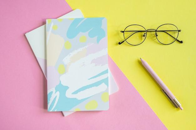 Widok z góry na okulary i długopis na żółtym tle i dwa zeszyty na różowym tle