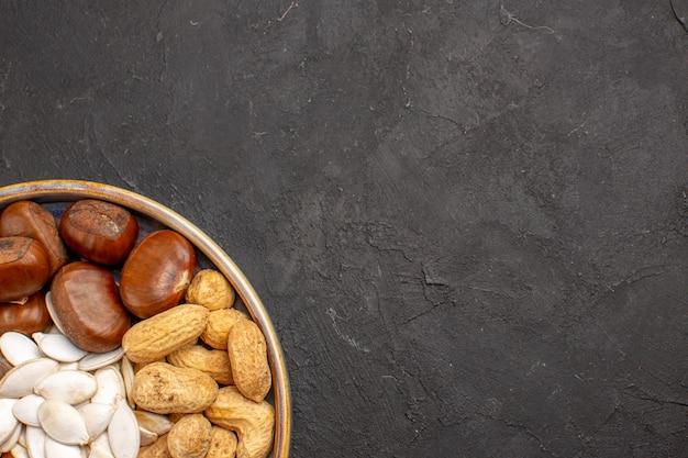 Widok z góry na orzechy włoskie, orzeszki ziemne, orzechy laskowe i inne na ciemnej powierzchni
