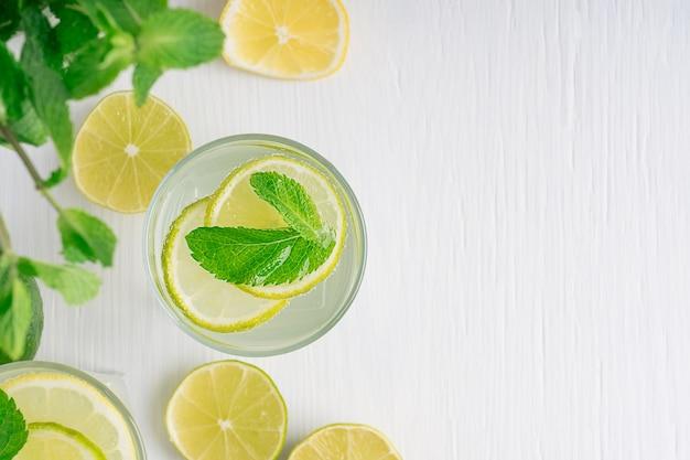 Widok z góry na orzeźwiającą lemoniadę z plasterków cytryny i limonki gazowanej wody i liści zielonej mięty