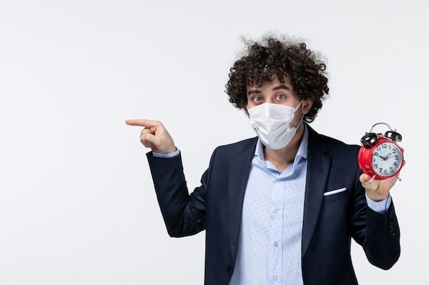 Widok z góry na osobę biznesową w garniturze i noszącą maskę trzymającą zegar wskazujący coś po prawej stronie