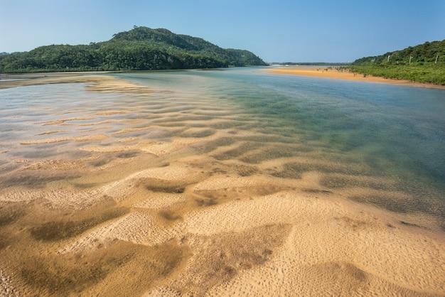 Widok z góry na oszałamiającą rzekę z płytkimi wodami, falistymi piaskami, górami i namorzynami. wyspa iriomote.
